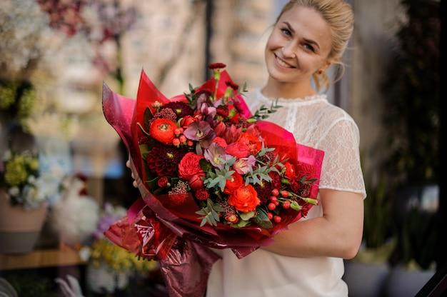 Ragazza sorridente che tiene un mazzo di fiori rossi cremisi