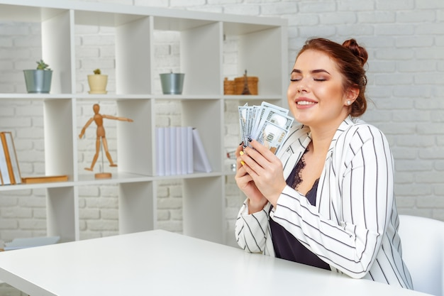 Ragazza sorridente con banconote del dollaro