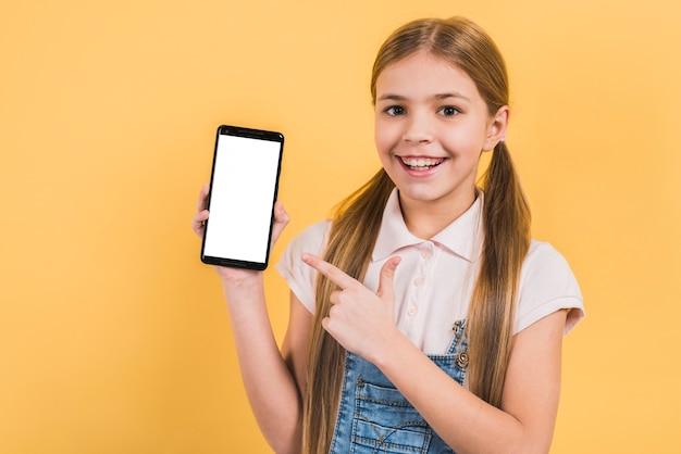 Ragazza sorridente con capelli biondi lunghi che indica la sua barretta al telefono mobile in bianco dello schermo bianco contro fondo giallo