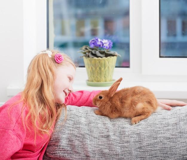 Ragazza sorridente con coniglio al coperto