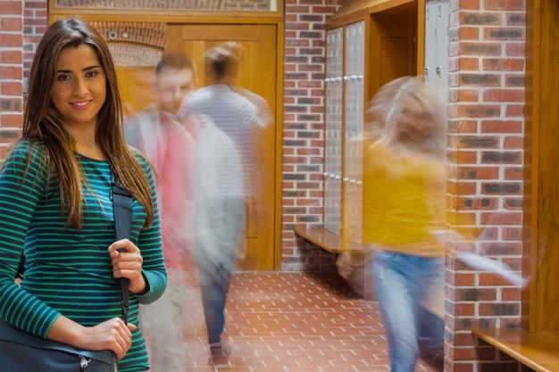 Ragazza sorridente con gli studenti offuscati che cammina attraverso il corridoio