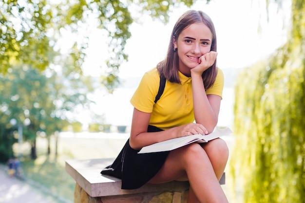 Ragazza sorridente con il libro nel parco