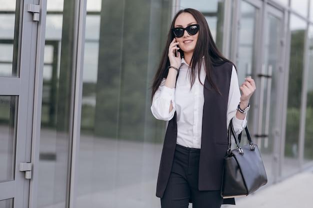 Ragazza sorridente con occhiali da sole e una borsa comunica sul suo telefono