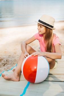 Ragazza sorridente con palla di vento in spiaggia
