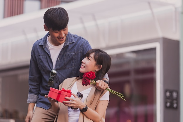 Ragazza sorridente con una scatola di cioccolatini e rose