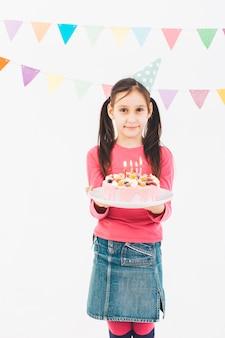 Ragazza sorridente con una torta di compleanno