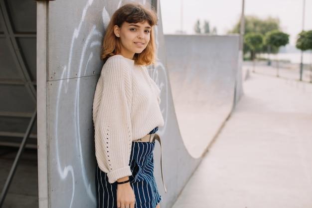 Ragazza sorridente dei latinos mentre stando da solo contro una parete su una via.
