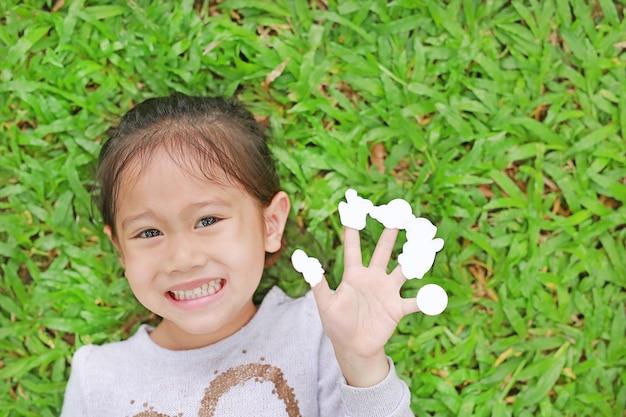 Ragazza sorridente del bambino che si trova sul prato verde dell'erba con la mostra degli autoadesivi bianchi vuoti