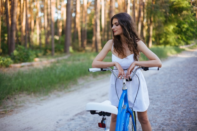 Ragazza sorridente del ritratto con una bici all'aperto nel giorno soleggiato