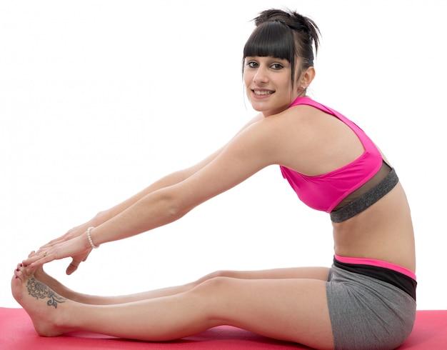 Ragazza sorridente della giovane donna che fa esercizio sul pavimento