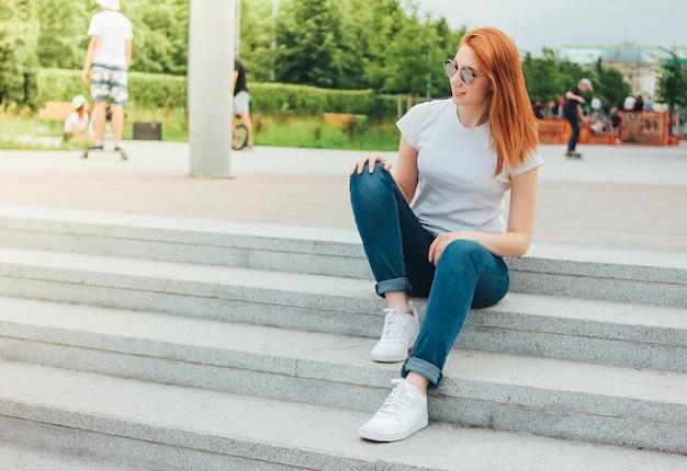 Ragazza sorridente della testarossa attraente in occhiali da sole rotondi in abbigliamento casual che si siede sulla via
