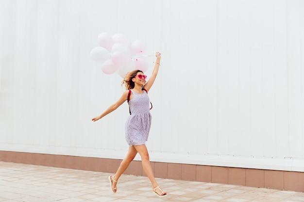 Ragazza sorridente emozionante in occhiali da sole rosa in esecuzione con palloncini, indossando abiti e sandali
