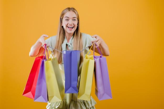 Ragazza sorridente felice che apre i sacchetti della spesa variopinti isolati sopra giallo