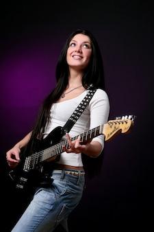 Ragazza sorridente felice che gioca chitarra