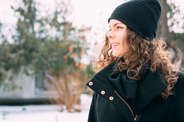 Ragazza sorridente felice con capelli ricci in un cappotto e cappello nel parco di inverno