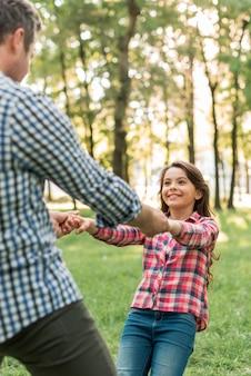 Ragazza sorridente graziosa che gioca con suo padre in parco