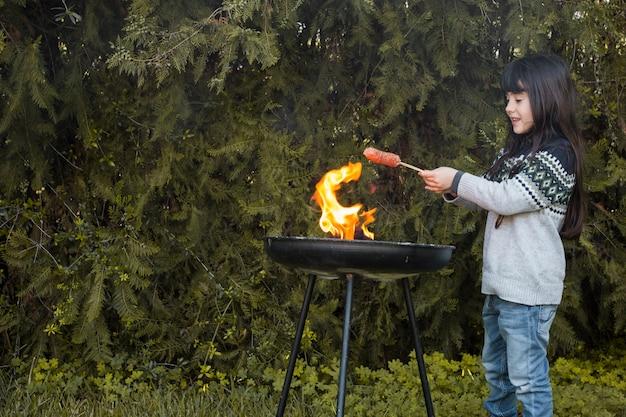 Ragazza sorridente grigliare salsicce sul barbecue portatile all'aperto