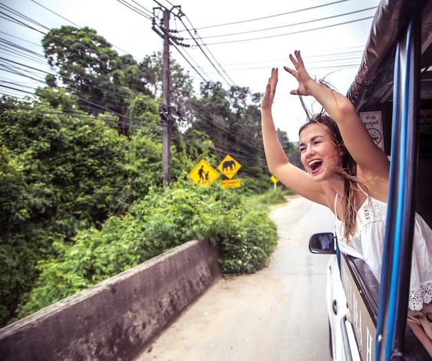 Ragazza sorridente guarda fuori dal finestrino di un taxi, tuk-tuk