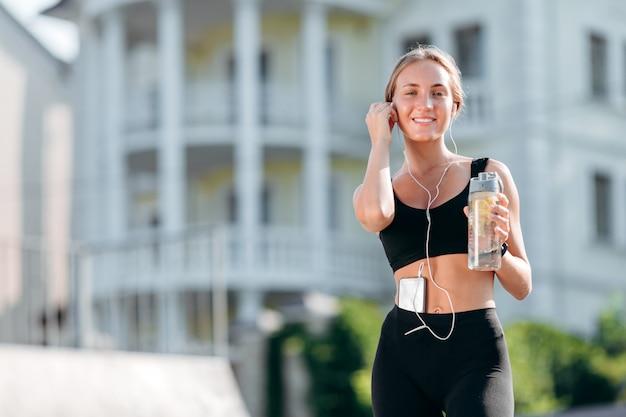 Ragazza sorridente in abiti sportivi neri con le cuffie che tengono una bottiglia di acqua.