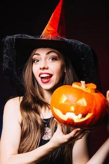Ragazza sorridente in cappello da strega con zucca