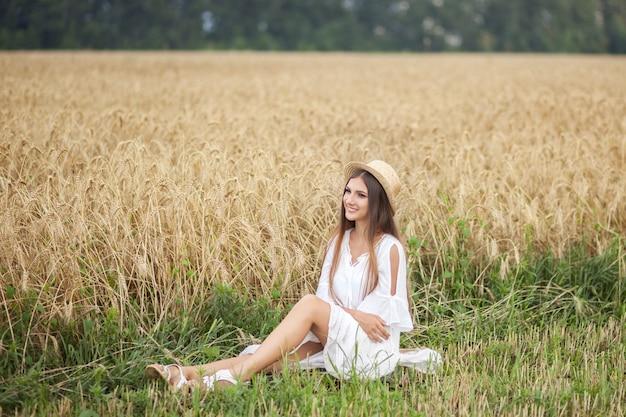 Ragazza sorridente in cappello di paglia e in vestito bianco che gode della natura del giacimento di grano. vacanze estive