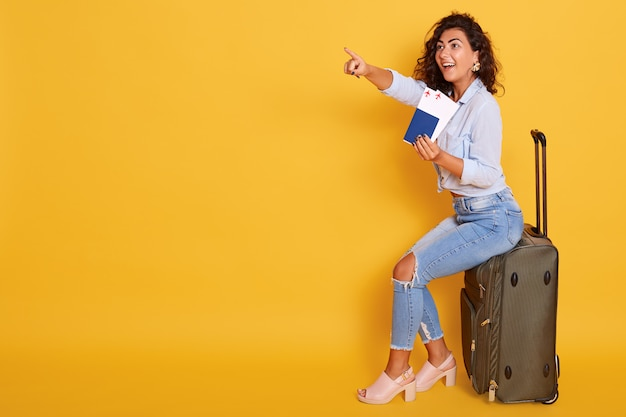 Ragazza sorridente in vestiti alla moda isolati sopra fondo rosa. passeggero che viaggia all'estero,