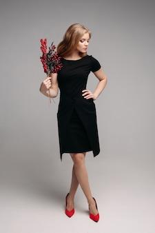 Ragazza sorridente in vestito nero che tiene ramo disponibile