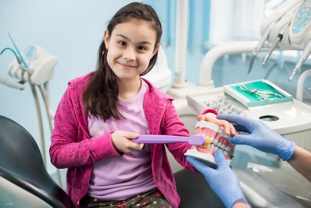 Ragazza sorridente nella sedia del dentista che mostra spazzolino da denti adeguato facendo uso del modello dentale della mascella e del grande spazzolino da denti nell'ufficio dentario