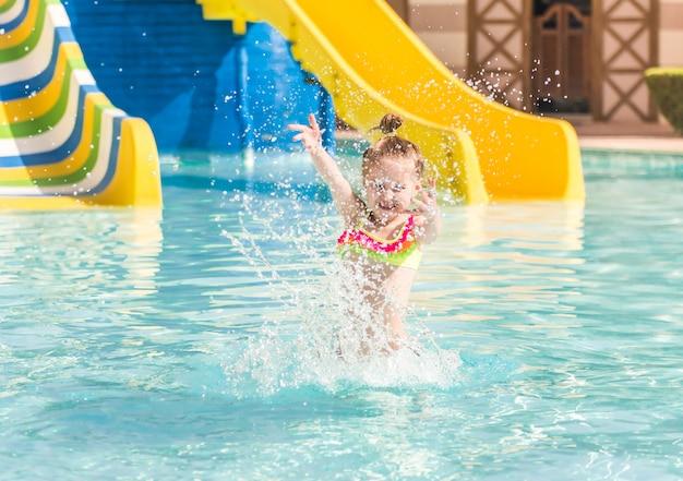Ragazza sorridente nuotare a bordo piscina