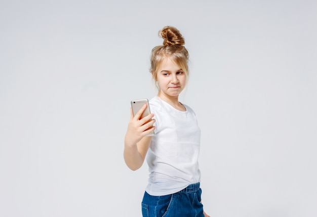 Ragazza sorridente spensierata del preteen con capelli biondi in maglietta bianca e jeans che fanno selfie, isolato su fondo bianco