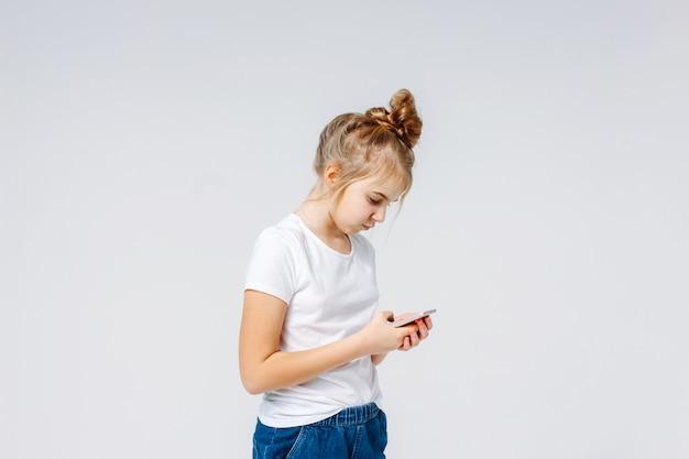 Ragazza sorridente spensierata del preteen con capelli biondi in maglietta bianca e jeans facendo uso del cellulare isolato su fondo bianco