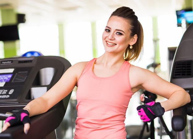 Ragazza sorridente sport atletico con corpo forma fitness in posa e relax in palestra