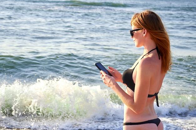 Ragazza sorridente sveglia che manda un sms con il suo messaggio di telefono cellulare su una spiaggia.