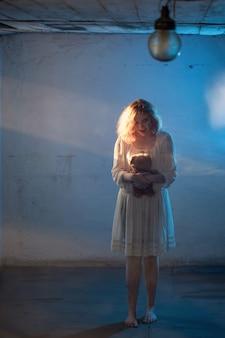 Ragazza spaventosa in abito bianco da film horror in camera
