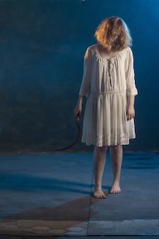 Ragazza spaventosa in abito bianco dal film horror in camera