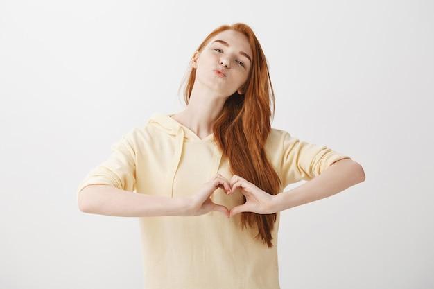 Ragazza splendida rossa che sorride e che mostra il gesto del cuore