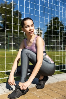 Ragazza sportiva allaccia le scarpe da ginnastica e distoglie lo sguardo