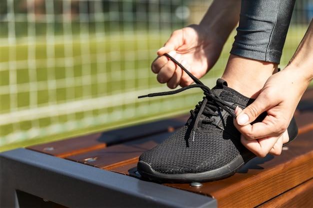 Ragazza sportiva allaccia le sue scarpe da ginnastica su una panchina