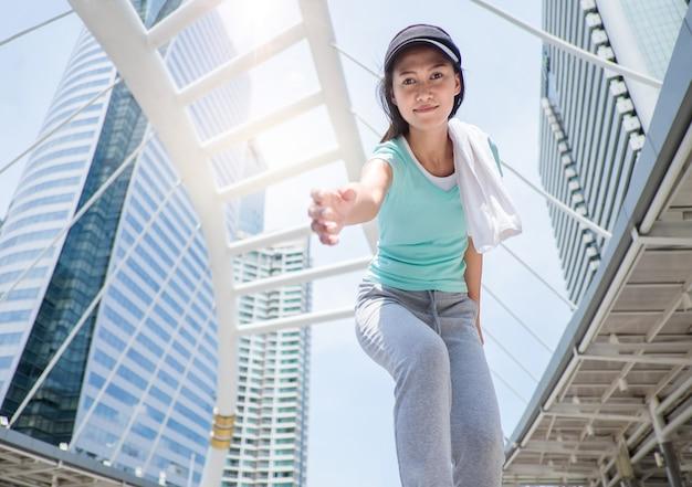 Ragazza sportiva che raggiunge la mano e cerca di aiutarti a stare in piedi.