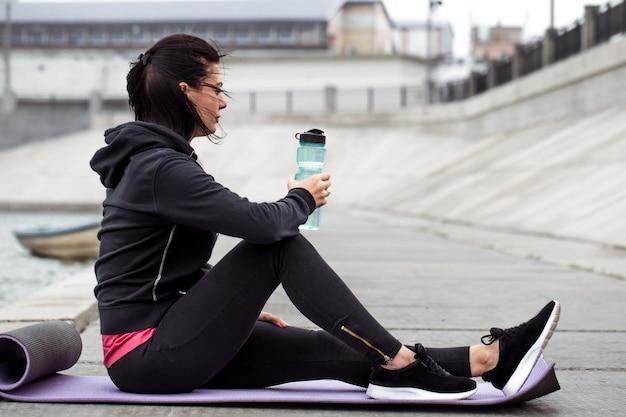 Ragazza sportiva che si siede con la bottiglia di acqua