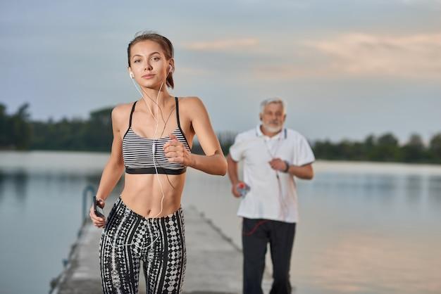 Ragazza sportiva con la figura adatta che corre vicino al lago nella sera. uomo anziano che corre dietro.