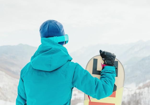 Ragazza sportiva con snowboard all'aperto