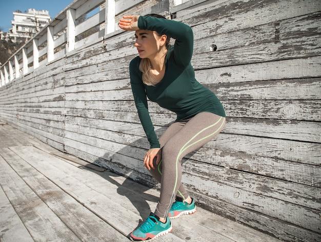 Ragazza sportiva di forma fisica che riposa dopo l'esercizio nell'abbigliamento di modo di sport, sport di concetto