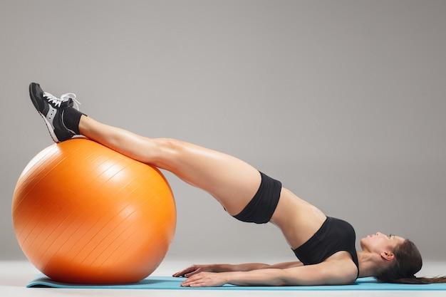 Ragazza sportiva facendo esercizi su un fitball