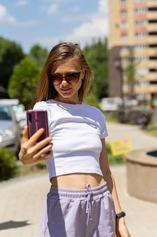 Ragazza sportiva in un top corto per strada prende un selfie