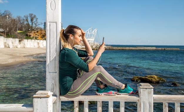 Ragazza sportiva sul molo con il telefono