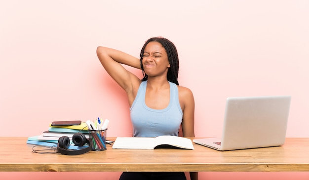 Ragazza studentessa adolescente afroamericano con capelli lunghi intrecciati nel suo posto di lavoro con mal di collo