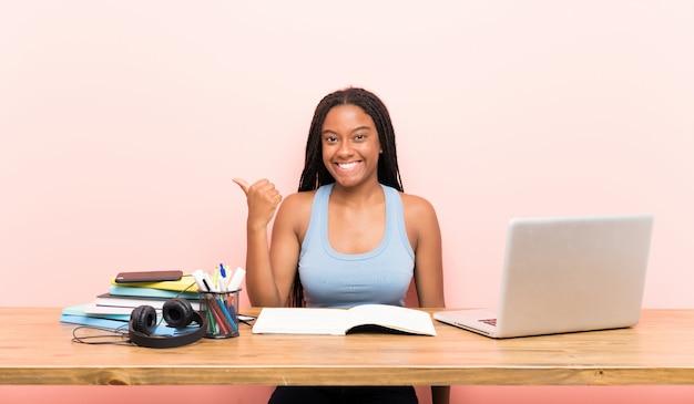 Ragazza studentessa adolescente afroamericano con i capelli lunghi intrecciati nel suo posto di lavoro che punta verso il lato per presentare un prodotto