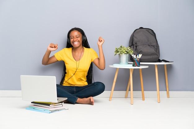 Ragazza studentessa afroamericana adolescente con capelli intrecciati lunghi seduto sul pavimento