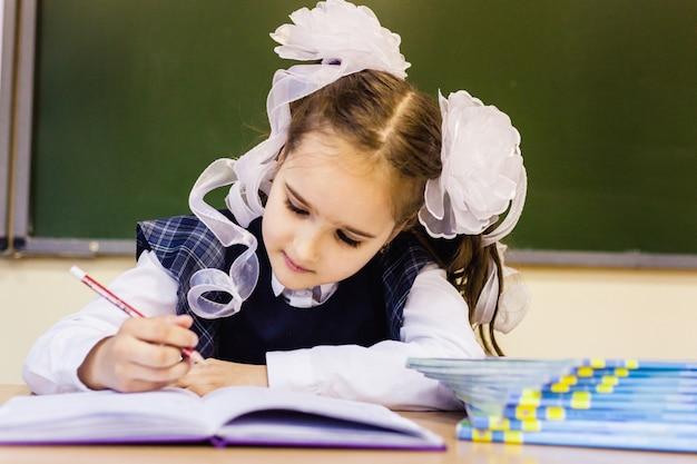 Ragazza studentessa e scuola. la ragazza indossa una divisa scolastica a scuola. formazione